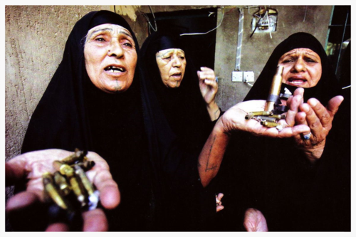 Women lamenting with bullet shells
